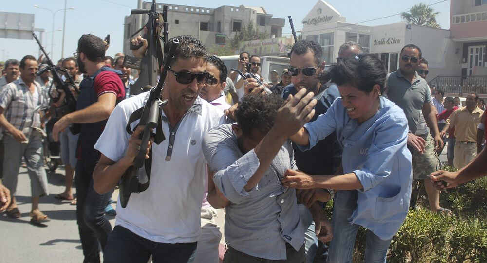 Police officers control the crowd (rear) while surrounding a man (front C) suspected to be involved in opening fire on a beachside hotel in Sousse, Tunisia, as a woman reacts(R), June 26, 2015