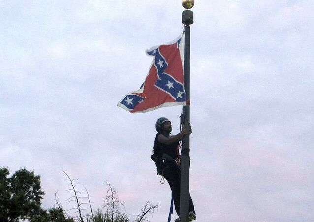 Bree Newsome of Charlotte, N.C., climbs a flagpole to remove the Confederate battle flag at a Confederate monument in front of the Statehouse in Columbia, S.C., on Saturday, June, 27, 2015.