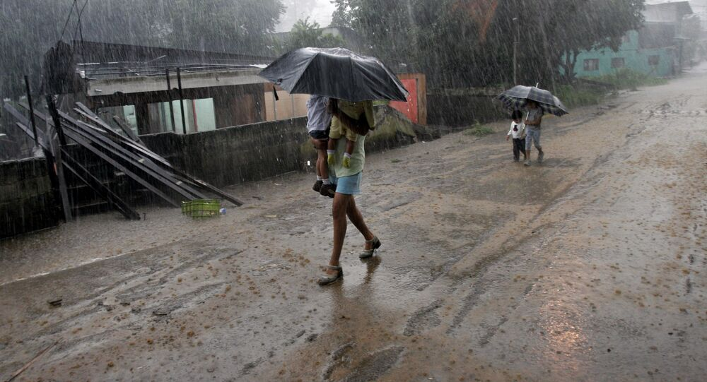A woman carries her children in the rain as she walks by homes destroyed by flooding in Alajuela, Costa Rica