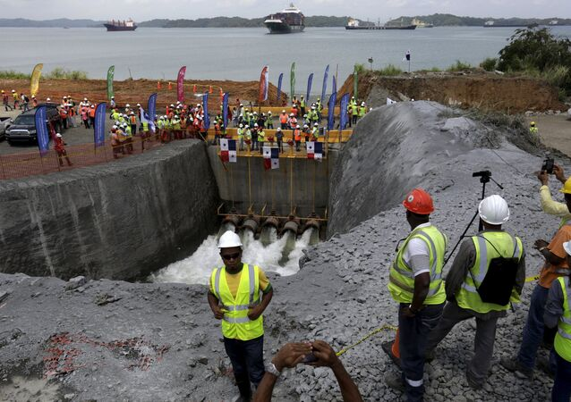 Workers look at the pipes as they flood the Panama Canal Expansion project on outskirts of Colon City June 11, 2015