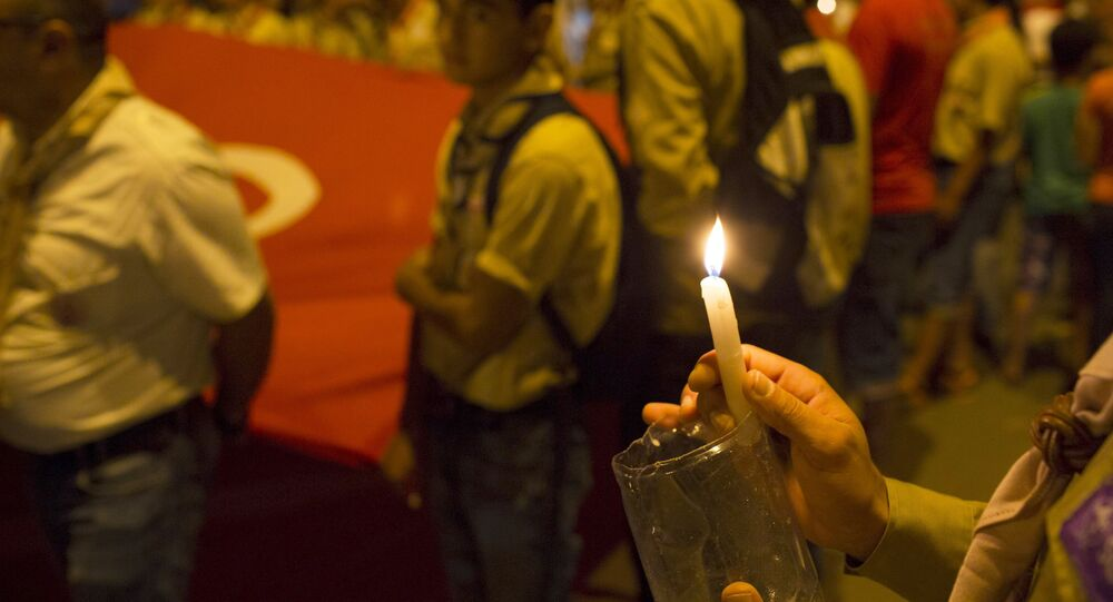 A boy scout holds a candle during a protest to condemn an attack by a gunman at the beach of the Imperial Marhabada hotel in Sousse, Tunisia, June 27, 2015