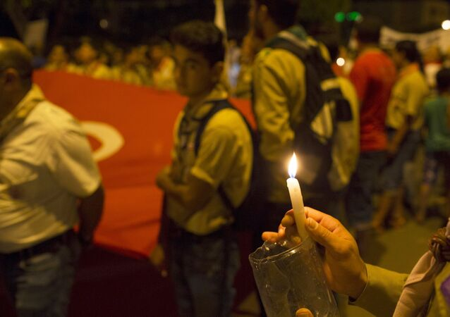 A boy scout holds a candle