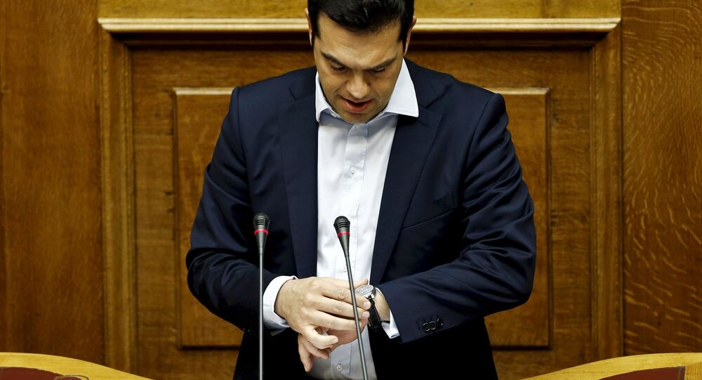 Greek Prime Minister Alexis Tsipras looks at his watch as he delivers a speech during a parliamentary session in Athens, Greece in this June 28, 2015