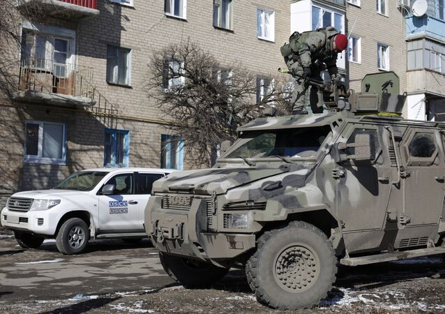 A Ukrainian serviceman stands on top of a KRAZ armoured vehicle close to a car of the Organization for Security and Cooperation in Europe (OSCE) in Soledar, Donetsk region. (File)