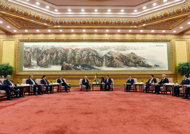 Chinese President Xi Jinping, center right, speaks to Swiss Economy Minister Johann Schneider-Ammann as he meets with delegates attending the signing ceremony for the Articles of Agreement of the Asian Infrastructure Investment Bank (AIIB) at the Great Hall of the People in Beijing