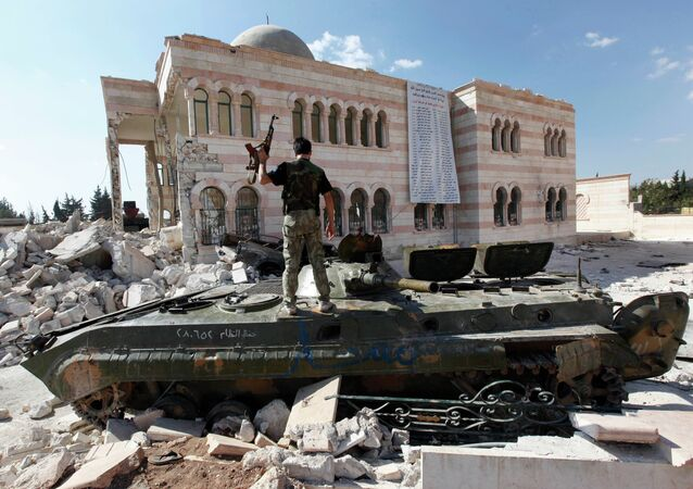 Free Syrian Army soldier stands on a damaged Syrian military tank in front of a damaged mosque, which were destroyed during fighting with government forces, in the Syrian town of Azaz.