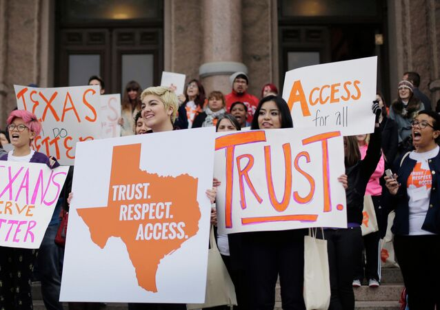 FILE - In this Feb. 26, 2015 file photo, college students and abortion rights activists hold signs during a rally on the steps of the Texas Capitol, in Austin, Texas. The Supreme Court refused on Monday, June 29, 2015, to allow Texas to enforce restrictions that would force 10 abortion clinics to close