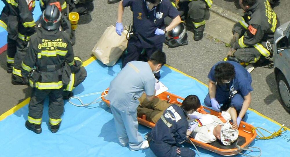 A passenger receives medical treatment from rescue workers after their Shinkansen bullet train made an emergency stop in Odawara, south of Tokyo, in this aerial view photo taken by Kyodo June 30, 2015