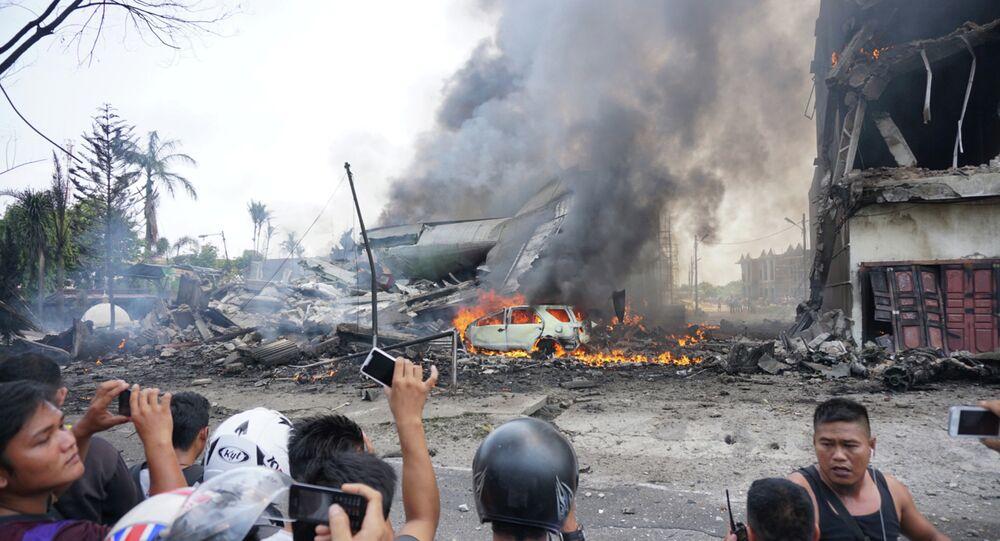 People look at a military plan crash in Medan