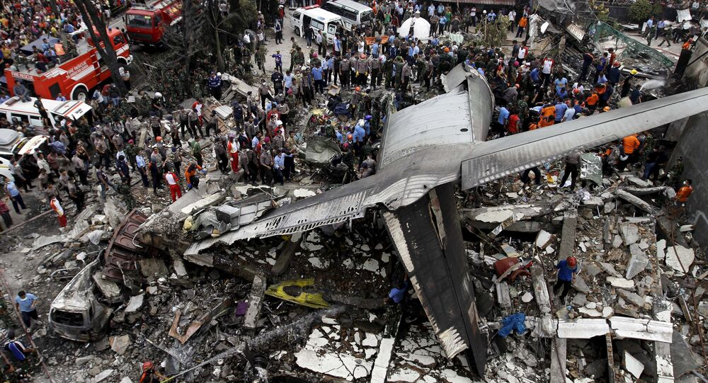 Security forces and rescue teams examine the wreckage of an Indonesian military C-130 Hercules transport plane after it crashed into a residential area in the North Sumatra city of Medan, Indonesia