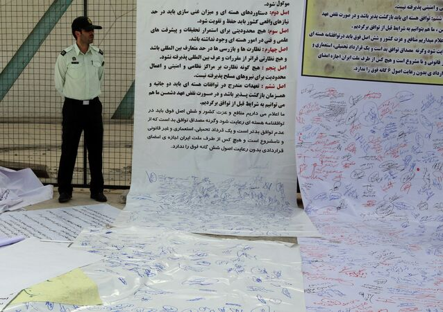 An Iranian policeman stands guard next to signed scrolls of paper at Tehran's Azadi Square (Freedom Square) on June 30, 2015, in support of the Iranian team pursuing a nuclear agreement with world powers