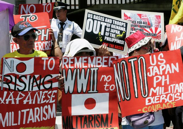 Protesters display placards during a rally outside the Japanese Embassy to protest the ongoing naval exercises by Japan and the United States.