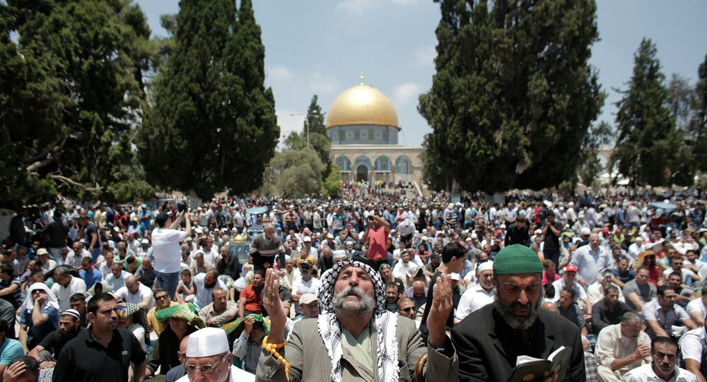 Palestinian Muslim worshipers pray outside the Dome of the Rock at the Al-Aqsa Mosque compound in Jerusalem during the second Friday prayer of the holy month of Ramadan, on June 26, 2015