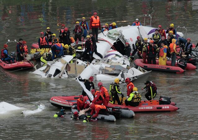 Emergency personnel retrieve the body of a passenger of a commercial plane after it crashed in the water in Taipei, Taiwan, Wednesday, Feb. 4, 2015