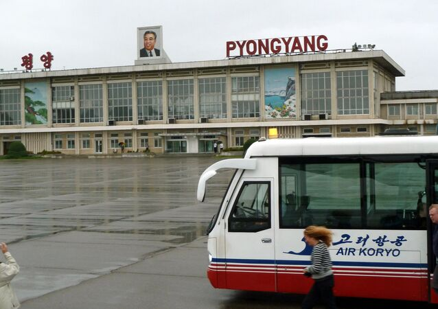 This photo taken on September 21, 2010 shows a foreign visitor (L) taking pictures of Pyongyang airport with a portrait of late North Korean leader Kim Il-Sung on the roof in Pyongyang