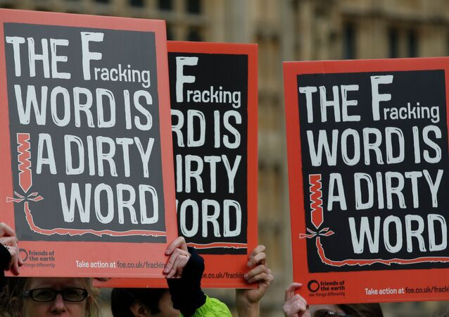 Demonstrators hold up placards as they take part in an anti-fracking protest outside the Palace of Westminster in London.