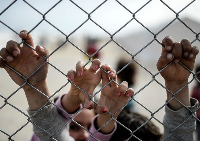 Hands of Syrian Kurdish children are seen holding a fence in a UNHCR (United Nations Refugee Agency) refugee camp on February 2, 2015, at Suruc, in Sanliurfa