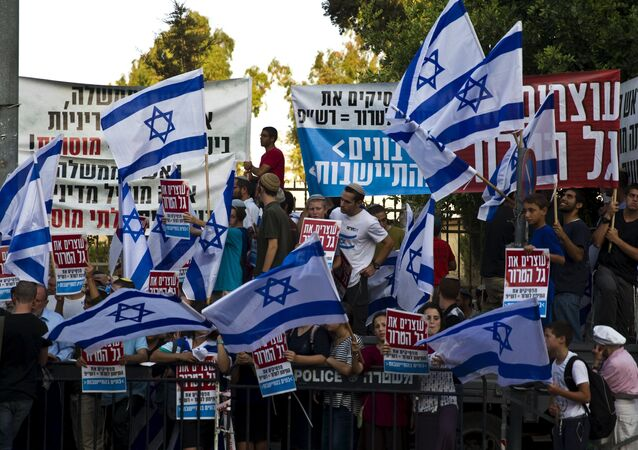 Right-wing activists hold Israeli national flags during a demonstration calling on the Israeli government to take action against recent violence in Jerusalem July 1, 2015
