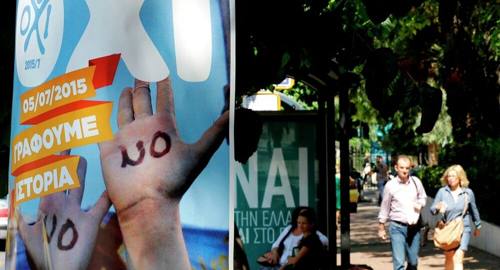 Commuters wait at a bus stop as the banner, left, reading ''NO, we are writing history'' and poster behind reading YES to Greece'' referring to the upcoming referendum in Athens, Thursday, July 2, 2015.