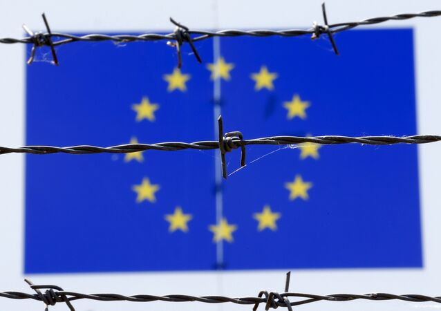 A barbed wire is seen in front of a European Union flag