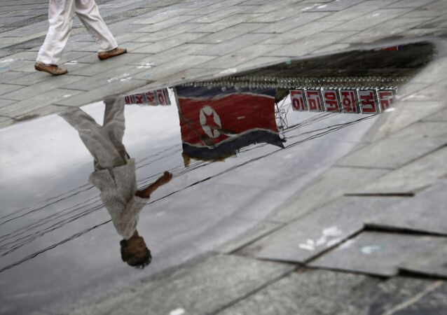 A North Korean woman is reflected in a rain puddle as she walks past the country's national flag along the Kim Il Sung Square on Sunday, July 21, 2013, downtown Pyongyang, North Korea