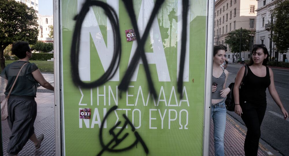 People walk past a YES poster sprayed with a graffiti reading ' NO' refering to upcoming controversial referendum in Athens on July 2, 2015