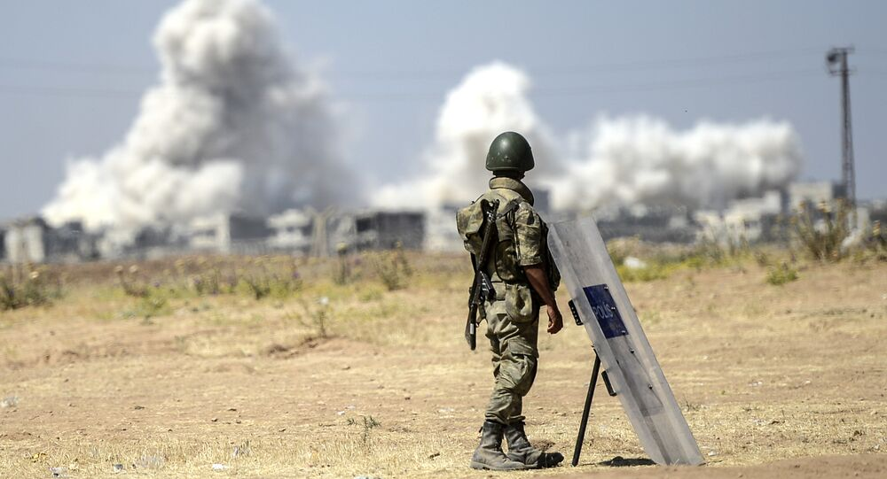 A picture taken from the Turkish side of the border in Suruc, Sanliurfa province, shows a Turkish solider standing as smoke rises from the Syrian town of Kobane, also known as Ain al-Arab, on June 27, 2015