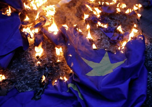Demonstrators burn a European Union flag during a rally supporting the no vote for the upcoming referendum outside the European Union office in Athens, Thursday, July 2, 2015.
