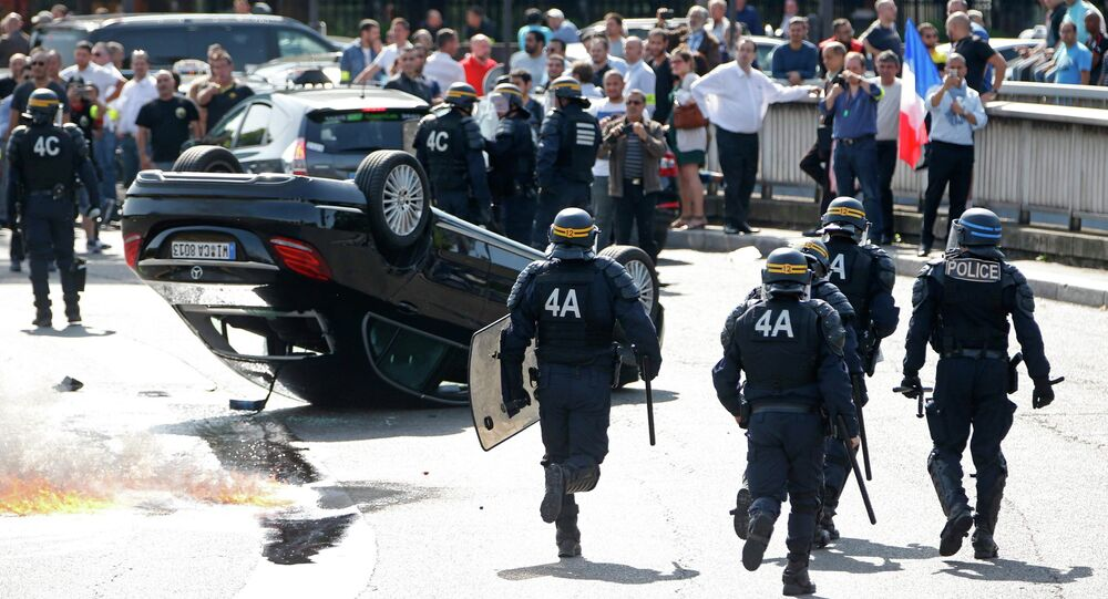French riot police stand next to an overturned car as striking French taxi drivers demonstrate at the Porte Maillot to block the traffic on the Paris ring road during a national protest against car-sharing service Uber, in Paris, France, June 25, 2015