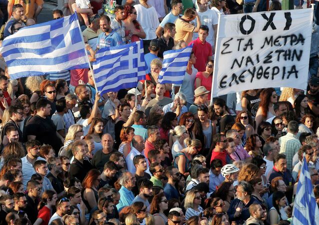 Demonstrators wave greek flags during an anti-austerity rally in front of the parliament building in Athens, Greece, July 3, 2015