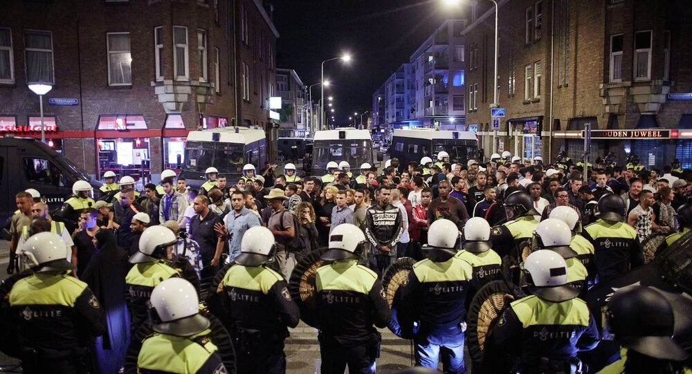 Dutch riot police surround detained suspects at Schilderswijk district in The Hague, Netherlands, in the early hours of Friday, July 3, 201
