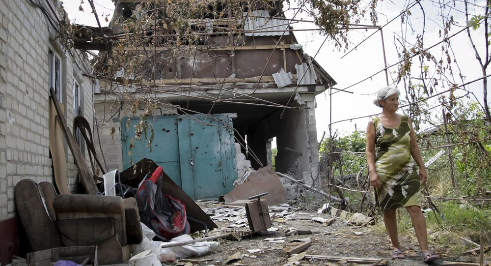 A woman walks in front of her damaged house, which according to locals was hit by shelling on Wednesday, the village of Sakhanka in Donetsk region, Ukraine, July 2, 2015