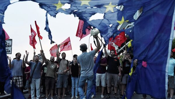 Members of left wing parties shout slogans behind a burning European Union flag during an anti-EU protest in the northern Greek port city of Thessaloniki, Sunday, June 28, 2015 - Sputnik International