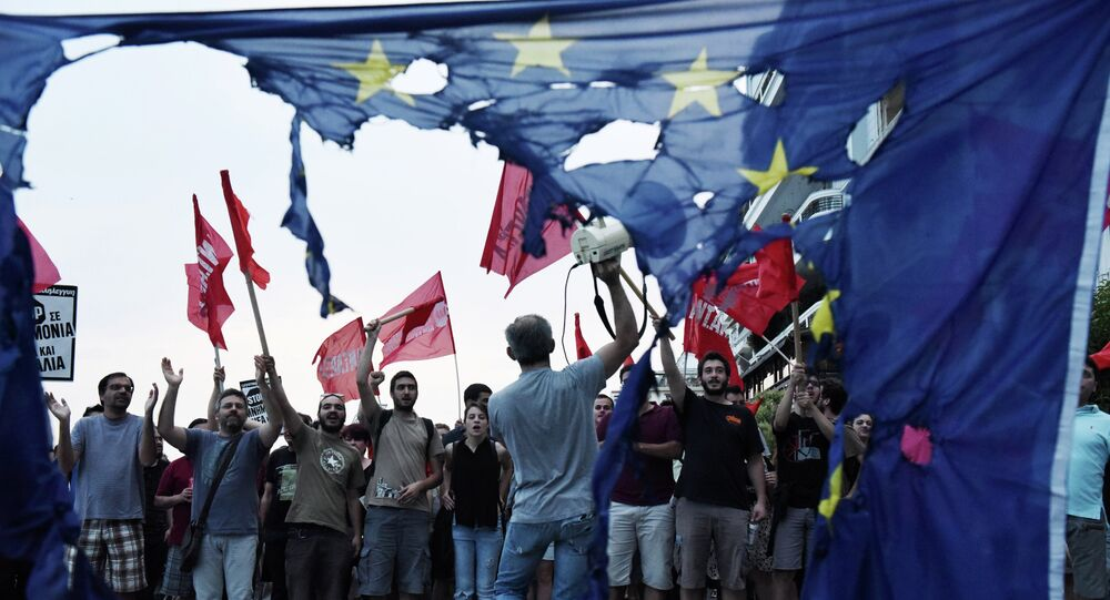 Members of left wing parties shout slogans behind a burning European Union flag during an anti-EU protest in the northern Greek port city of Thessaloniki, Sunday, June 28, 2015