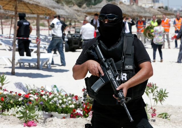 A hooded Tunisian police officer stands guard ahead of the visit of top security officials of Britain, France, Germany and Belgium at the scene of Friday's shooting attack in front of the Imperial Marhaba hotel in the Mediterranean resort of Sousse, Tunisa, Monday, June 29, 2015
