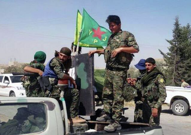 In this photo provided by the Kurdish fighters of the People's Protection Units (YPG), which has been authenticated based on its contents and other AP reporting, Kurdish fighters of the YPG, sit on their pickup in the town of Ein Eissa, north of Raqqa city, Syria, Tuesday, June 23, 2015