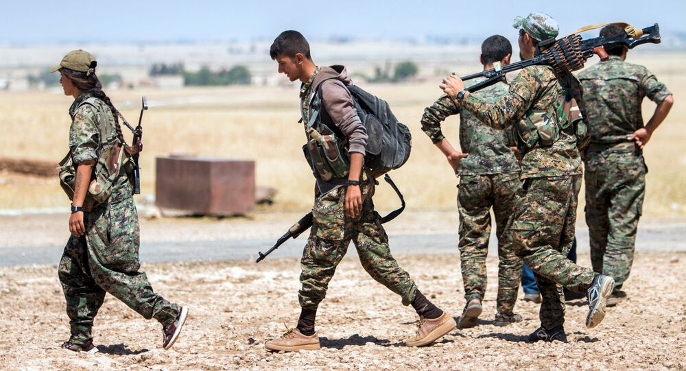 Kurdish People's Protection Units (YPG) fighters walk with their weapons at the eastern entrances to the town of Tal Abyad in the northern Raqqa countryside, Syria, June 14, 2015