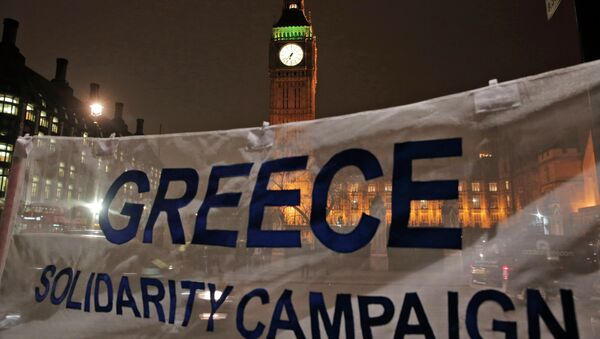 Backdropped by the Houses of Parliament in central London, protesters hold a banner at a rally to show solidarity with Greece. File photo - Sputnik International