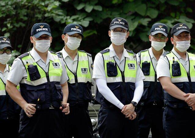Police officers wearing masks as a precaution against Middle East Respiratory Syndrome (MERS) stand guard during a rally in Seoul, South Korea