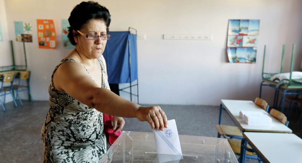A woman casts her vote at a polling station in Athens, Sunday, July 5, 2015