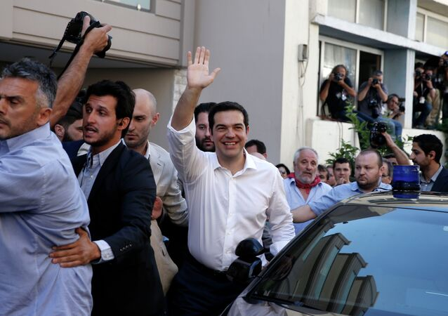 Greece's Prime Minister Alexis Tsipras waves to his supporters after voting outside a polling station in Athens, Sunday, July 5, 2015