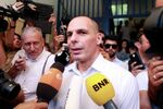 Greek Finance Minister Yanis Varoufakis is surrounded by media as he leaves a polling station during a referendum in Athens, Greece July 5, 2015