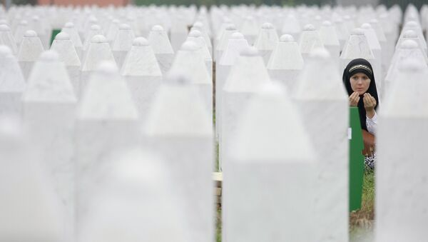 Bosnian woman Merima Nukic prays at the grave of her father during a funeral ceremony at the memorial center in Potocari, near Srebrenica, 160 kms east of Sarajevo, Bosnia - Sputnik International