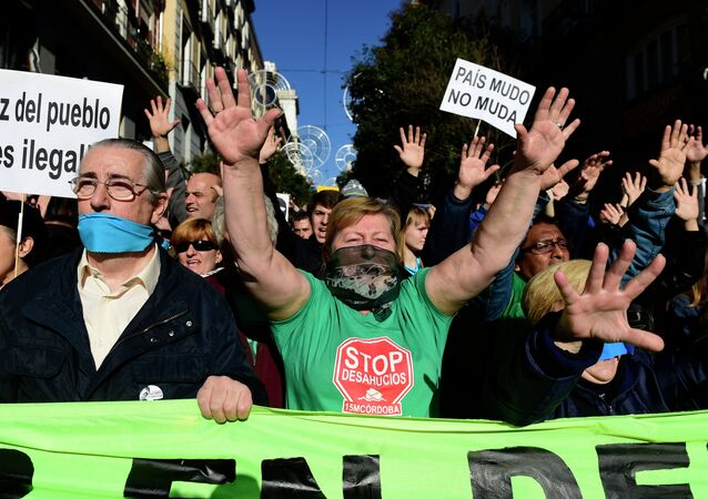 Demonstrators hold placards reading A country with a gag doesn't move as they protest against the new public security law (ley mordaza) approved by the lower house of parliament, in Madrid on December 20, 2014