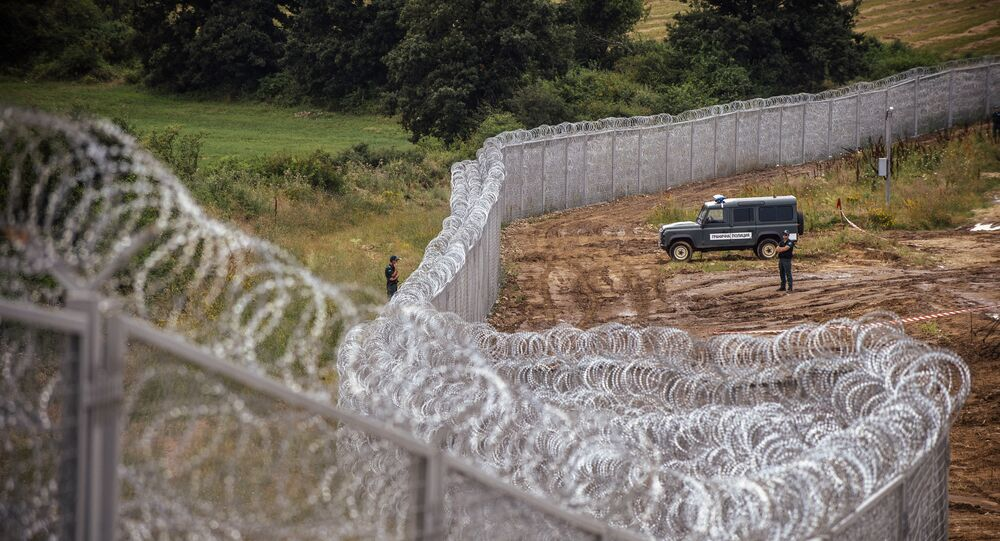 Border policemen stand guard next to a barbed wire wall on the Bulgarian border with Turkey, near the village of Golyam Dervent