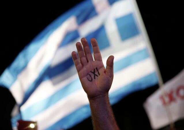 In this July 3, 2015 file photo, a demonstrator raises his hand with the word ''No'' written on it as a Greek flag waves behind during a rally organized by supporters of the No vote in Athens.