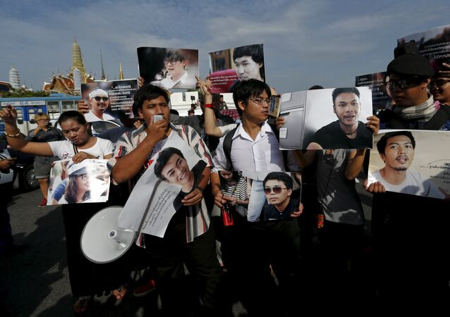 Members of the New Democracy Movement activist group and supporters hold up pictures of the 14 students who had been held for holding anti-coup protests, during a rally outside the military court in Bangkok.