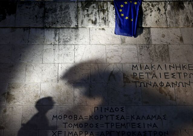 An European Union flag is pictured as people are silhouetted on the Tomb of the Unknown Soldier during a rally in front of the Greek parliament