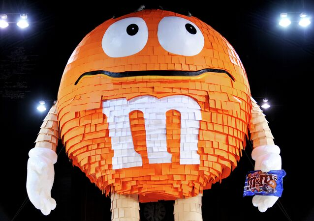 A 46 foot (14 meter) piñata in the form of an orange M&M candy, filled with thousands of M&M's pretzel packages