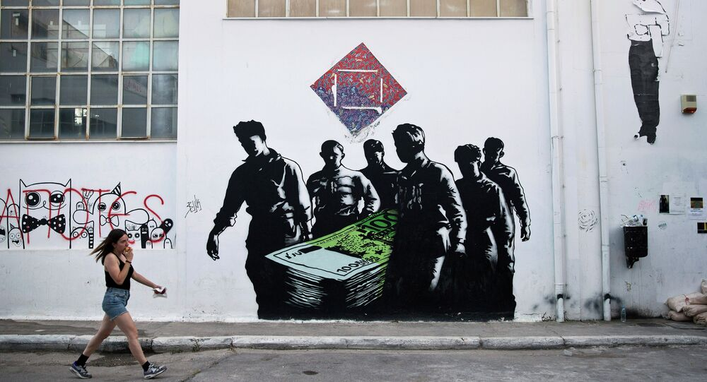 In this photo taken on Wednesday, June 17, 2015, a woman walks past a graffiti artwork titled Death of Euros made by French street artist Goin at the Athens School of Fine Arts